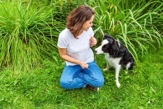 Het glimlachen het jonge aantrekkelijke vrouw spelen met leuke puppyhond border collie in de zomertuin of stadspark openlucht. meisje training truc met hond vriend. dierenverzorging en dieren concept.