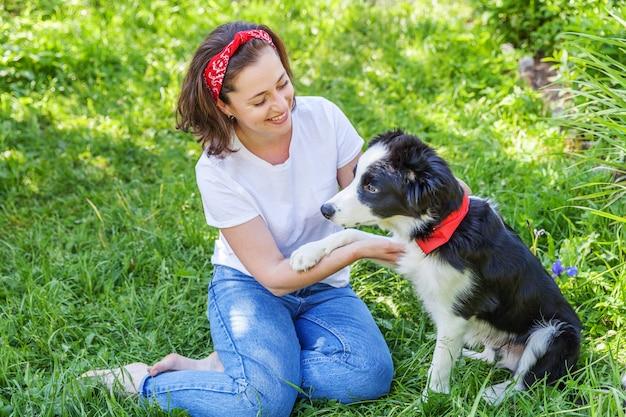 Het glimlachen het jonge aantrekkelijke vrouw spelen met leuke puppyhond border collie in tuin of stadspark