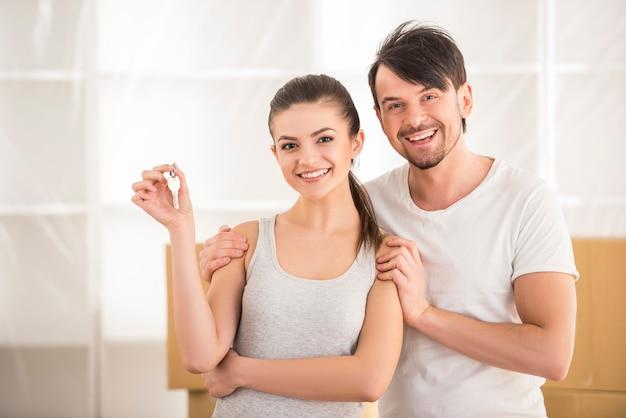 Het glimlachen het jonge paar tonen sleutels van hun nieuw huis.