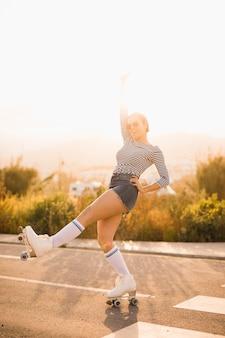 Het glimlachen het jonge vrouw in evenwicht brengen op de rolschaats tegen helder zonlicht