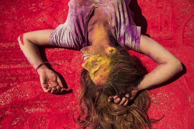 Het glimlachen het jonge vrouw ontspannen op rood holikleurpoeder