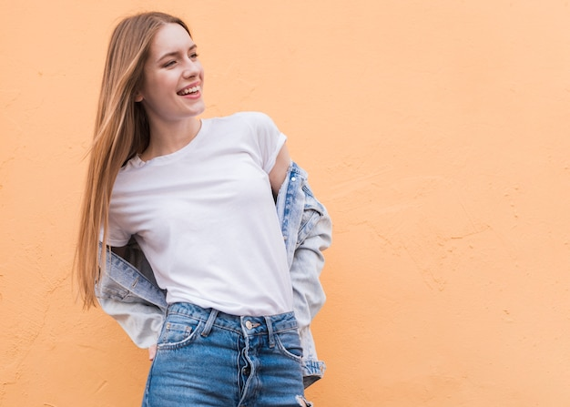 Het glimlachen het jonge vrouwelijke model stellen op beige geweven muur