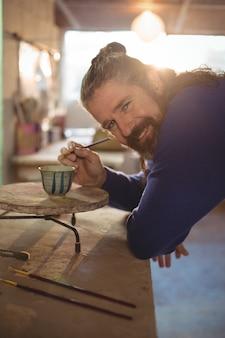 Het glimlachen het mannelijke pottenbakker schilderen op kom