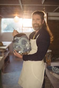 Het glimlachen het mannelijke pottenbakker schilderen op pot