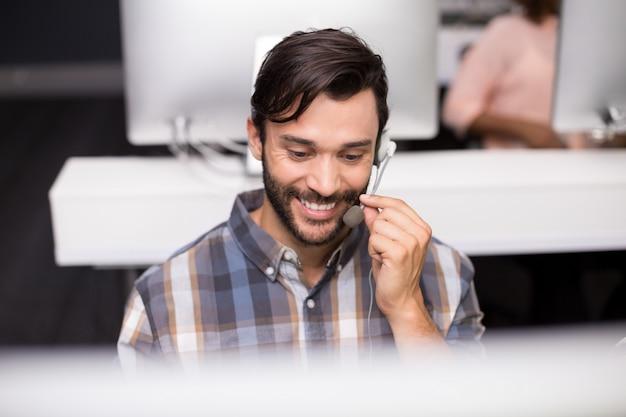 Het glimlachen het mannelijke uitvoerende spreken van de klantendienst op hoofdtelefoon bij bureau