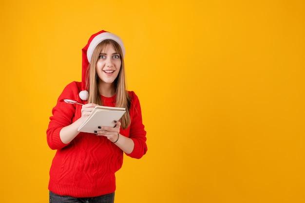 Het glimlachen het notitieboekje van de meisjesholding het schrijven nota's en nieuwe jaarplannen met pen die santahoed draagt