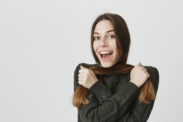 Het glimlachen het vrolijke donkerbruine vrouw spelen met haar en het lachen