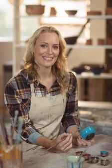 Het glimlachen het vrouwelijke pottenbakker schilderen op kom