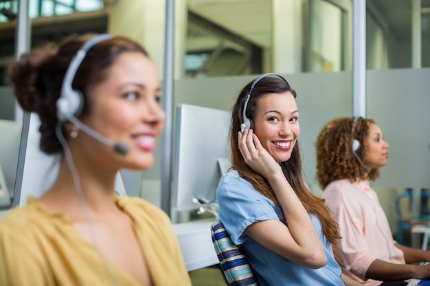 Het glimlachen het vrouwelijke uitvoerende spreken van de klantendienst op hoofdtelefoon bij bureau