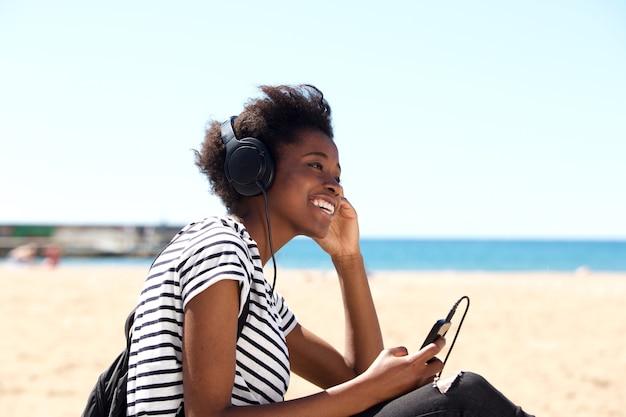 Het glimlachen jonge vrouwenzitting in openlucht het istening aan muziek op hoofdtelefoons