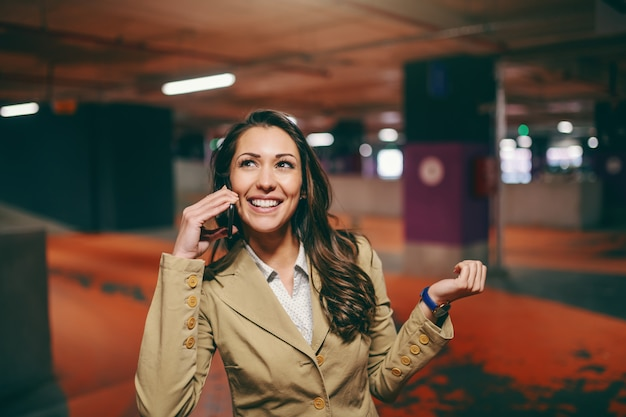 Het glimlachen kaukasisch brunette kleedde elegant gebruikend slimme telefoon en bekijkend omhoog ondergronds parkeren.