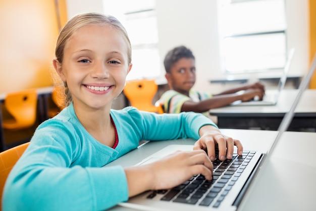 Het glimlachen leerling het stellen met laptop bij bureau in klaslokaal