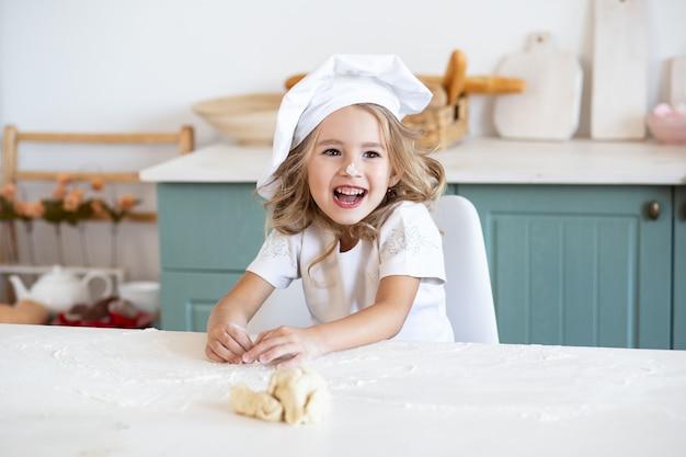 Het glimlachen meisje het spelen met deeg voor koekjes op keuken