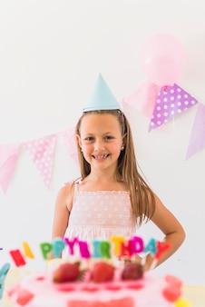 Het glimlachen meisje het stellen achter verjaardagscake in partij