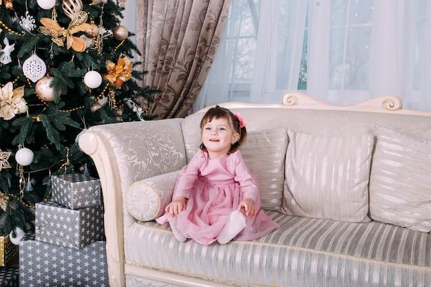 Het glimlachen meisjezitting op bank dichtbij kerstboom binnen. vrolijk kerstfeest en een gelukkig nieuwjaar!