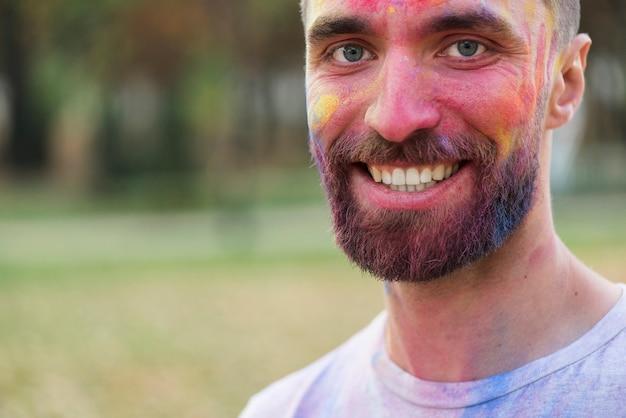 Het glimlachen mens het stellen met geschilderd gezicht bij holi