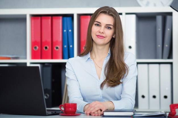 Het glimlachen onderneemsterzitting bij een bureau in de bureau juiste schouder vooruit. handen op tafel. in de camera kijken.