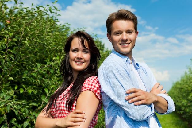 Het glimlachen paar het stellen in fruitboomgaard