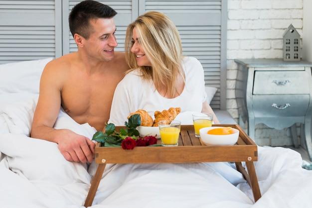 Het glimlachen paarzitting op bed dichtbij ontbijt aan boord
