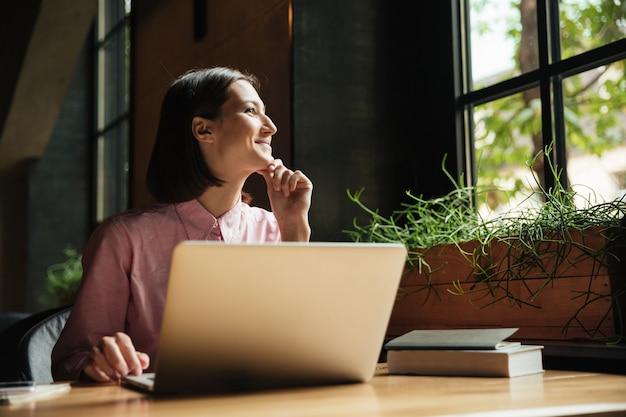 Het glimlachen peinzende vrouwenzitting door de lijst in koffie