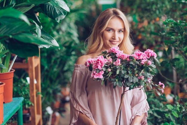 Het glimlachen portret van de holdingsinstallatie van de blonde jonge vrouw met roze bloemen in de tuin