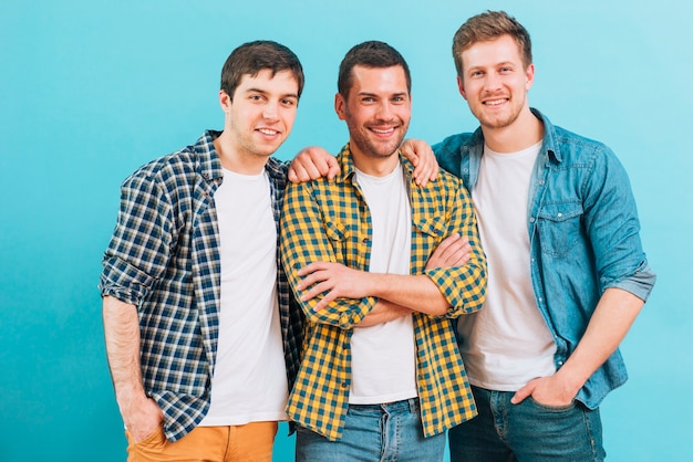Het glimlachen portret van drie mannelijke vrienden die zich tegen blauwe achtergrond bevinden