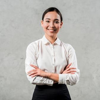 Het glimlachen portret van een aziatische jonge vrouw met haar gekruiste wapens het kijken aan camera tegen grijze concrete muur