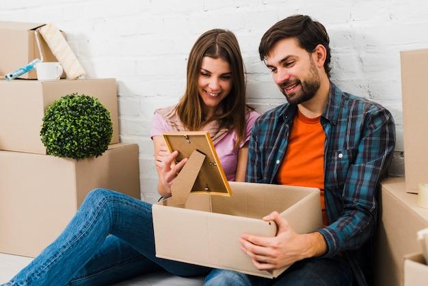 Het glimlachen portret van een jong paar dat frame bekijkt dat uit kartondoos wordt genomen