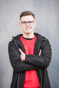 Het glimlachen portret van een jonge mens die zwart jasje met zijn die wapens dragen tegen concrete achtergrond worden gekruist