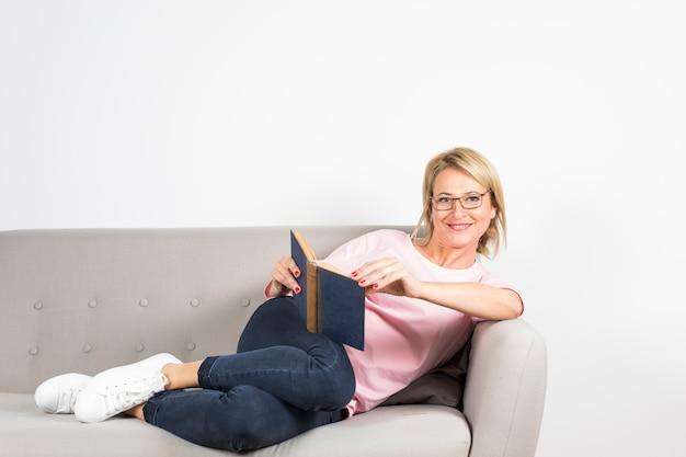 Het glimlachen portret van een rijp boek van de vrouwenholding het in hand leunen op bank tegen witte achtergrond