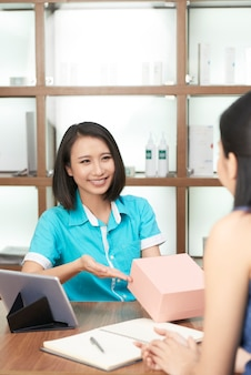 Het glimlachen salonbeheerder aanwezig geven aan cliënt