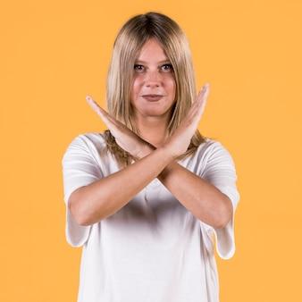 Het glimlachen schakelt vrouw uit die waarschuwingsgebaar in gebarentaal tonen tegen gele achtergrond