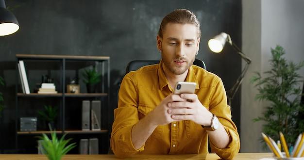 Het glimlachen smartphone van de jonge mensenholding dient binnen bureau in.