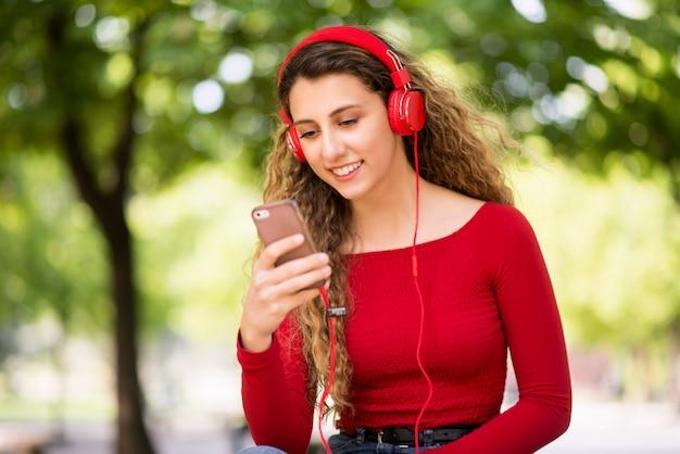 Het glimlachen tiener het luisteren muziek van telefoon