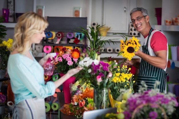 Het glimlachen van bloemist bespuitend water op bloemen in bloemenwinkel