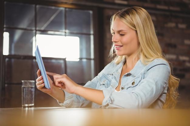 Het glimlachen van blonde wat betreft op tabletcomputer