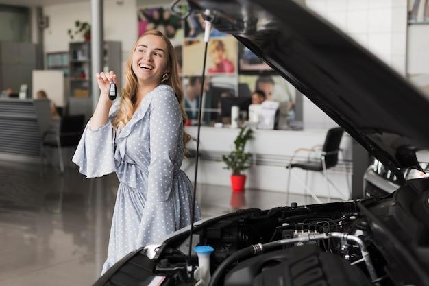 Het glimlachen van de autosleutels van de blondevrouw