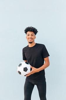 Het glimlachen van de bal van de voetbalsterholding en het bekijken camera