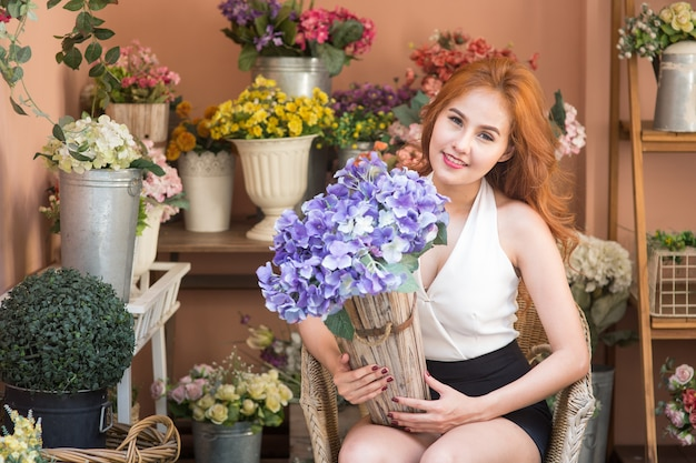 Het glimlachen van de holdingsboeket van de vrouwenbloemist bij kleine bedrijfsbloemwinkel
