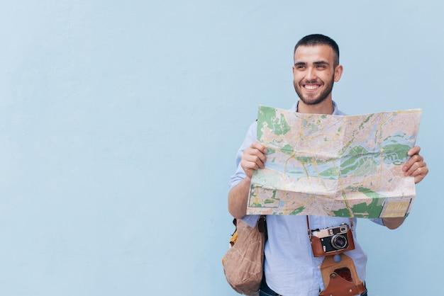Het glimlachen van de holdingskaart van de reizigersfotograaf en weg kijkend status tegen blauwe achtergrond