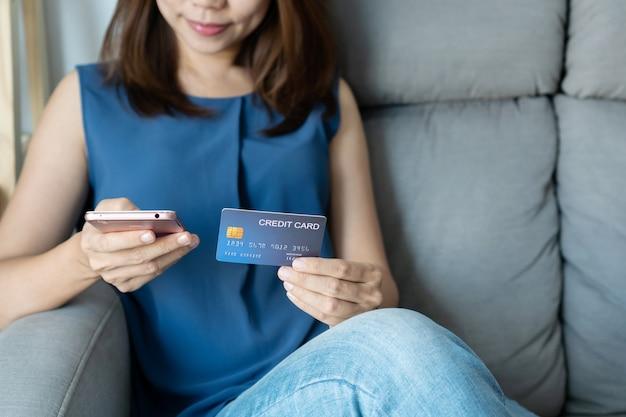 Het glimlachen van de jonge aziatische creditcard van de vrouwenholding terwijl thuis het gebruiken van mobiele telefoon en het zitten op bank, digitale levensstijl met technologie, elektronische handel, het winkelen online concept.
