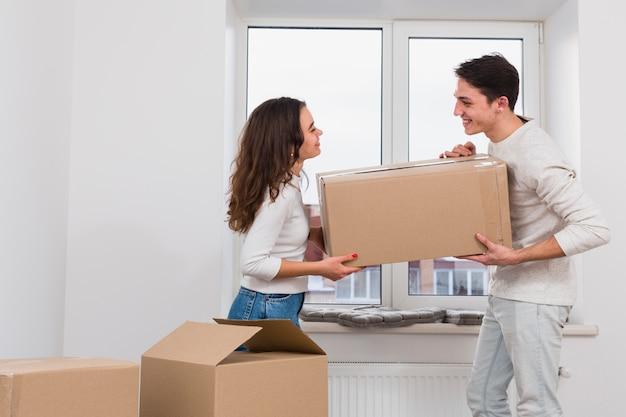 Het glimlachen van de jonge doos van het paar dragende karton in nieuwe flat