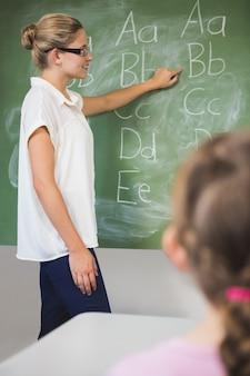 Het glimlachen van de jonge geitjes van het leraarsonderwijs op bord in klaslokaal