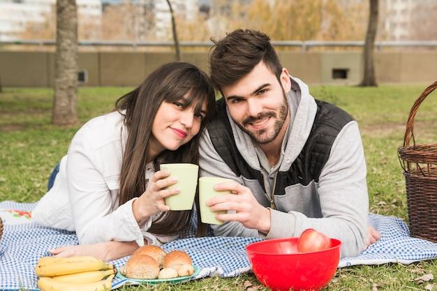 Het glimlachen van de jonge glazen van de paarholding in picknick bij park