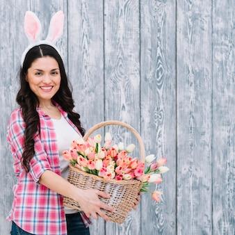 Het glimlachen van de mand van de vrouwenholding van roze tulpenmand tegen grijze houten achtergrond
