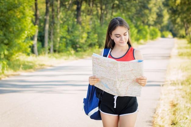 Het glimlachen van de mooie rugzak van de meisjesholding op haar schouder die de kaart bekijken die alleen in het platteland reizen