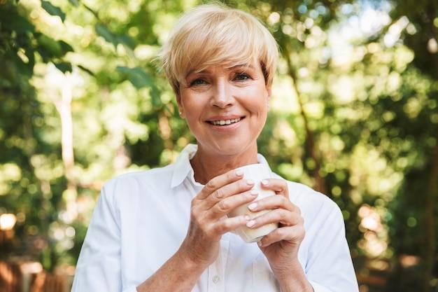 Het glimlachen van de rijpe kop van de vrouwenholding van koffie