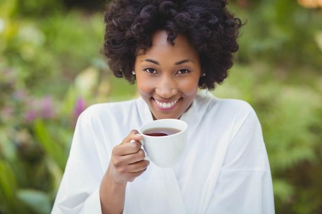 Het glimlachen van de thee van de vrouwenholding in de tuin