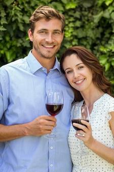 Het glimlachen van de wijnglazen van de paarholding bij voortuin