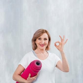 Het glimlachen van de yogamat van de geschiktheidsvrouw en het tonen van ok teken met vingers tegen grijze muur